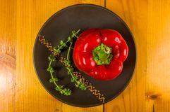 A freshest red paprika, bell pepper in ceramic plate. With basil flowers on wooden background, close up stock photo