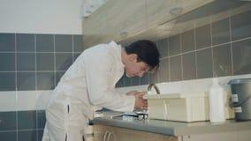 Freshing framsida för trött doktor med vatten från klappet i det medicinska laboratoriumet 4K arkivfilmer