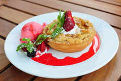 Freshly baked apple crumble pie. With various berries, mint leaf and strawberry ice cream on a white plate stock image