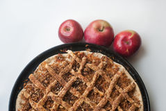 Freshly baked apple pie with apples. In the background Stock Images
