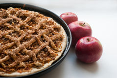 Freshly baked apple pie with apples. In the background Stock Photo