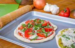 Freshly baked artisan pizza with fresh produce and cheese. Stock Image