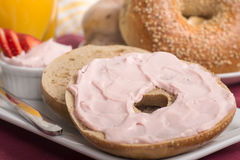 Freshly baked bagel with strawberry cream cheese, orange juice a Stock Image