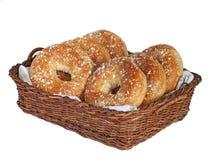 Freshly baked bagels. Six freshly baked multigrain bagels in wicker basket isolated on white royalty free stock photo