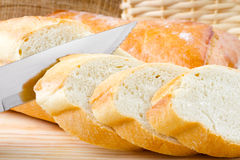 Freshly baked baguette sliced on cutting board Royalty Free Stock Photos