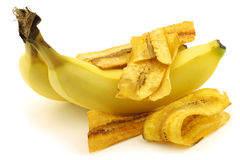 Freshly baked banana chips and fresh bananas Stock Images