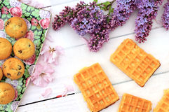 Freshly baked belgium waffles on romantic wooden table with lilac flowers Stock Images