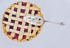 A freshly baked berry pie. A silver spatula sitting on top of a freshly baked berry pie with lattice crust Stock Images