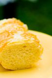 Freshly baked bread. A close up on freshly baked bread on a yellow plate Stock Image
