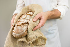 Freshly baked bread from the baker. Baker holding fresh bread in the hands. Stock Photo
