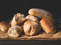 Freshly baked bread on burlap dark wooden background Stock Images