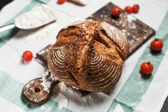 Freshly baked bread, flour and tomatoes on a wooden board on a kitchen towel on a table Stock Photography