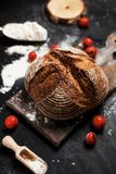 Freshly baked bread, flour and tomatoes on a wooden board on a table Stock Image