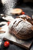 Freshly baked bread, flour and tomatoes on a wooden board on a table Royalty Free Stock Images