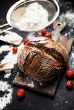 Freshly baked bread, flour and tomatoes on a wooden board on a table Royalty Free Stock Image