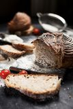 Freshly baked bread, flour and tomatoes on a wooden board on a table Royalty Free Stock Photography