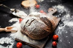 Freshly baked bread, flour and tomatoes on a wooden board on a table royalty free stock photo