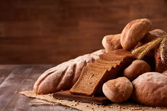 Freshly baked bread loaves on burlap on wooden table with brown blurred background. Texture closeup bakery products. Wheat. Slice of bread on the board Stock Photography