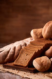 Freshly baked bread loaves on burlap on wooden table with brown blurred background. Texture closeup bakery products. Wheat. Slice of bread on the board Royalty Free Stock Photography