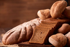 Freshly baked bread loaves on burlap on wooden table with brown blurred background. Texture closeup bakery products. Wheat. Slice of bread on the board Stock Photos