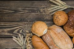 Freshly baked bread products on wooden background royalty free stock photography