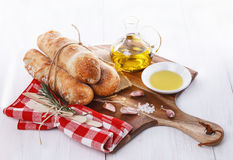 Freshly baked bread rolls and oil. Stone Baked Pane Di Casa bread rolls and aromatic oil on a white wooden background stock photos