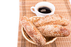Freshly baked bread rolls with sesame with cup of coffee Royalty Free Stock Images