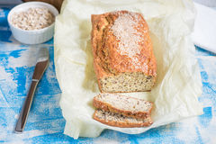 Freshly baked bread with sesame, bran and flax seeds on a wooden. Freshly baked bread with bran from oat flour with sesame seeds and flax seeds, on paper for Royalty Free Stock Photos