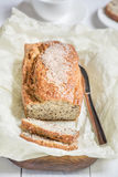 Freshly baked bread with sesame seeds on a wooden board on a lig. Freshly baked bread with bran from oat flour with sesame seeds and flax seeds, on paper for Stock Photography