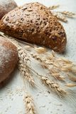 Freshly baked bread with spikelets of cereals in a country setting royalty free stock photography