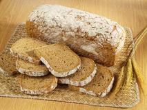 Freshly baked bread on table. Freshly baked bread and wheat on table royalty free stock photos