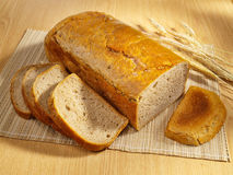 Freshly baked bread on table. Freshly baked bread and wheat on table stock photo