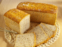 Freshly baked bread on table. Freshly baked bread and wheat on table royalty free stock photography