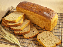 Freshly baked bread on table. Freshly baked bread and wheat on table royalty free stock photo