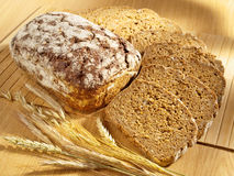 Freshly baked bread on table. Freshly baked bread and wheat on table royalty free stock images