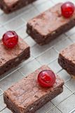 Freshly baked brownies with glace cherries. On a cooling tray Royalty Free Stock Photo