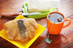 Freshly baked bun and cup of tea for breakfast Royalty Free Stock Photos