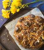Freshly baked buns with pine nuts, berries and caramel lying on the table. With napkin and flowers Royalty Free Stock Photography
