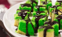 Colourful cake slices with chocolate syrup stock images