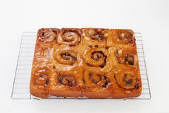 Freshly glased chelsea buns on a wire cooling rack - viewed from royalty free stock photo