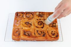 Freshly baked chelsea buns on a wire cooling rack being glazed royalty free stock photos