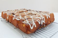 Freshly baked chelsea buns on a wire cooling rack - viewed from stock photos