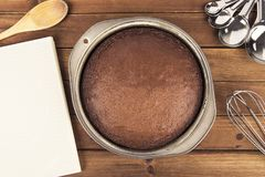 Freshly baked chocolate cake, cooking book and utensil. Disposed on wooden table. Top view Stock Photos