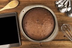 Freshly baked chocolate cake, tablet and utensil disposed on wooden table. royalty free stock image