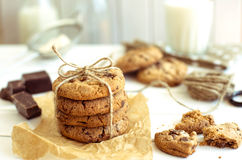 Freshly baked chocolate chip cookies with glass of milk on rustic wooden table. Stock Images
