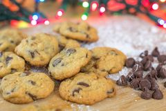 Freshly baked chocolate chip cookies on wooden board with colored lights in background Stock Photography