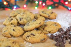 Freshly baked chocolate chip cookies on wooden board with colored lights Royalty Free Stock Images