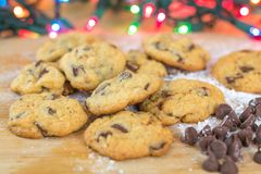 Freshly baked chocolate chip cookies on wooden board with colored lights Stock Photos
