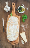 Freshly baked ciabatta bread with garlic, mediterranean olives, basil and Parmesan cheese on serving board over rustic Royalty Free Stock Image