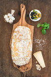 Freshly baked ciabatta bread with garlic, mediterranean olives, basil and Parmesan cheese on serving board over rustic Royalty Free Stock Images
